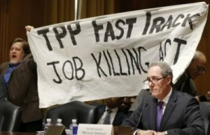 TPP-Protest-Froman-miffed-as-KZ-and-Dick-Ochs-hold-banner-behind-him.-Source-Reuters.-e1429808714476